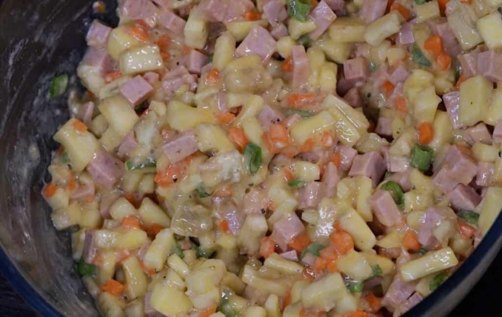 combine carrots, chopped spring onion, egg, flour, salt, and pepper